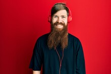 Redhead Man With Long Beard Listening To Music Using Headphones With A Happy And Cool Smile On Face. Lucky Person.