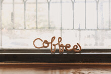 Fancy Wire Shaped Into Word COFFEE Stand On The Edge Of Cafe Window.