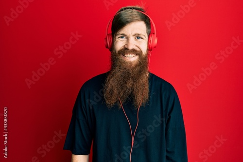 Papel de parede Redhead man with long beard listening to music using headphones with a happy and cool smile on face