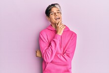 Young Hispanic Man Wearing Casual Pink Sweatshirt Smiling Looking Confident At The Camera With Crossed Arms And Hand On Chin. Thinking Positive.