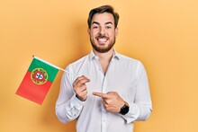Handsome Caucasian Man With Beard Holding Portugal Flag Smiling Happy Pointing With Hand And Finger