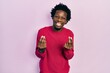 Young african american man wearing casual clothes doing money gesture with hands, asking for salary payment, millionaire business