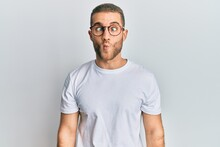 Young Caucasian Man Wearing Casual Clothes And Glasses Making Fish Face With Lips, Crazy And Comical Gesture. Funny Expression.