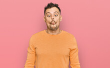 Young Hispanic Man Wearing Casual Clothes Making Fish Face With Lips, Crazy And Comical Gesture. Funny Expression.