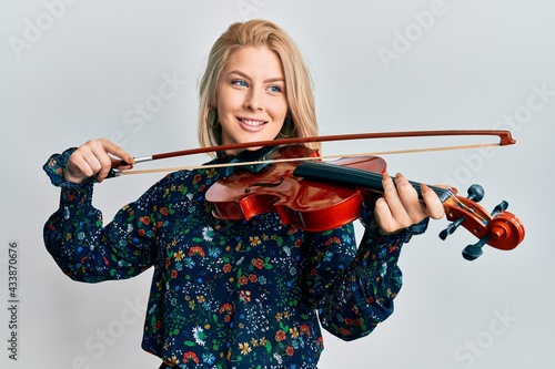 Young blonde woman playing violin smiling looking to the side and staring away thinking Fototapet