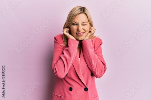Fotografering Middle age caucasian woman wearing business jacket covering ears with fingers with annoyed expression for the noise of loud music