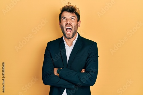 Fotografie, Obraz Handsome man with beard wearing business suit with arms crossed gesture and king crown angry and mad screaming frustrated and furious, shouting with anger looking up