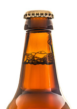 Neck Of A Brown Beer Bottle With Cap Showing The Bubbles On A White Background