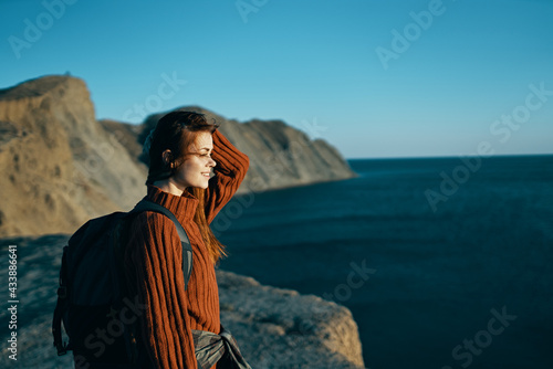 Fototapeta pretty woman in a sweater with a backpack near the sea in nature obraz