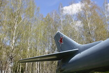 The Tail Fin And Stabilizer Of A Soviet Turbojet Military Aircraft Against The Background Of A Birch Grove And A Clear Blue Sky, A Monument To Russian Long-range Aviation