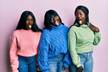 Three Young African American Friends Wearing Wool Winter Sweater Sticking Tongue Out Happy With Funny Expression. Emotion Concept.