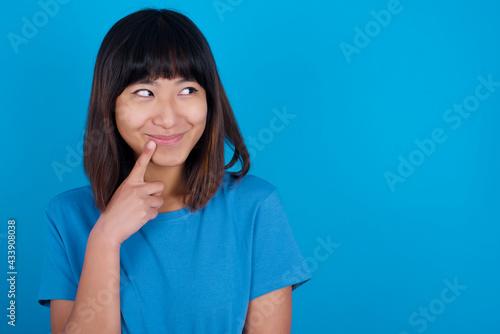 Fototapeta Lovely dreamy young beautiful asian girl wearing blue t-shirt against blue background keeps finger near lips looks aside copy space