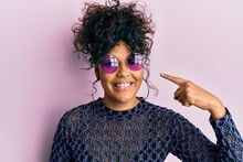 Young Hispanic Woman Wearing Cool Sunglasses Smiling Happy Pointing With Hand And Finger