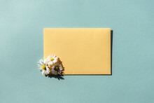Yellow Envelope And A Bouquet Of Daisies On Blue Background. Flat Lay Template For Greeting Card, Copy Space