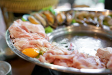 Closeup Jaew Hon Or Isan Hot Pot With Raw Egg Pork And Seafood With Boiling Spicy Thick Soup In Silver Ware Pot For Lunch Or Dinner And Thai Street Food At Restaurant
