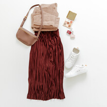 Folded Clothes For Women Fashion Urban Basic Outfit. Female Spring Look Autumn Outfit Burgundy Skirt Beige Sweater White Shoes Sneakers Bag, Make Up Cosmetics On White Background Flat Lay Square