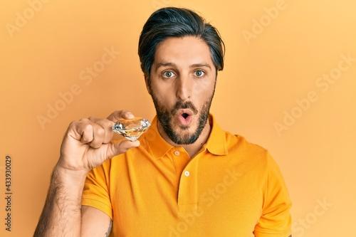 Fotografia Young hispanic man holding brilliant diamond stone scared and amazed with open m