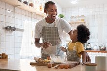 Happy Black African American Father And Little Son Smiling And Laughing While Cooking In Kitchen.