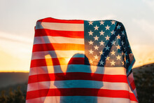 Independence Day. Silhouette Of Woman Holds An American Flag In Her Hands, Raised Above Her Head. Back View. In The Background, Sunset And Mountains. The Concept Of American National Holidays