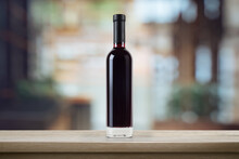 Red Wine Bottle, On A Wooden Empty Tabletop In Front Of A Blurred Background Of Cafe Interior. Wine Bottle Mockup. 3d Illustration.