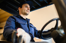 A Construction Worker Driving A Forklift In An Industrial Plant