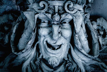 Monster Face Of AGreek Antique God Daimon Of Eager Rivalry, Envy, Jealousy, And Zeal Zelus (Zelos). Fragment Of An Ancient Stone Statue.