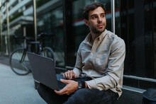 Handsome Man Using Laptop Outdoors