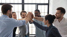 Business Team Of Happy Motivated Staff Employees Giving Joined Hands High Fives. Excited Work Group Celebrating Corporate Financial Success, Good Sales Result, Successful Teamwork And Achievement