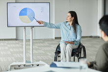 Portrait Of Successful Businesswoman In Wheelchair Leading Team Meeting And Pointing At Digital Whiteboard In Office, Copy Space
