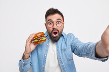 Surprised Bearded Man Makes Selfie Holds Appetizing Hamburger Looks Stunned At Camera Dressed In Stylish Denim Shirt Feels Very Hungry Eats Junk Food Isolated Over White Background. Diet Concept