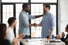 Happy African American Male Boss Welcoming New Hired Employee, Team Applauding. Business Leader Expressing Recognition, Appreciation, Acknowledge, Giving Handshake To Proud Worker