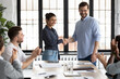 Happy Indian female team leader shaking hands with proud employee, thanking promoted worker for good job and congratulating with reward. Millennial business group welcoming newcomer with applause