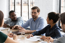 Satisfied Millennial Employee Sharing Ideas With Diverse Team On Office Brainstorming Meeting, Speaking And Smiling. Mentor Training Multiethnic Group Of Interns, Talking To New Hired About Job Tasks