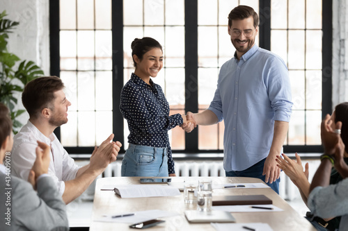 Valokuva Happy Indian female team leader shaking hands with proud employee, thanking promoted worker for good job and congratulating with reward