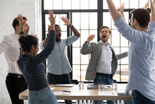 Happy Excited Millennial Employees Shouting For Joy, Raising Hands For Emotional High Fives. Business Team Of Overjoyed Professionals Cheering, Celebrating Good Sales Result, Financial Goal Achieving