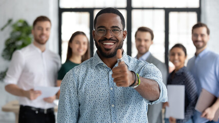 Portrait of happy African American male business leader making thumb up like gesture at camera. Employee satisfied with job and work with great team. Client giving positive feedback to company service