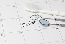 Dentist Appointment Reminder On Calendar With Toothbrush And Dental Tools. Concept Of Oral Health, Dental Exam And Teeth Cleaning