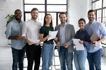 Portrait of happy diverse group of interns or students and corporate teacher after successfully passes exam. Multi ethnic business team of employees holding paper documents, looking at camera, smiling