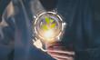 Leinwandbild Motiv Hand holding light bulb with power plug and show trees, renewable energy icons with sustainable development.