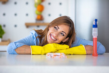 Young Smiling Woman In Gloves Cleaning House. Closeup Of Happy Beautiful Girl Wearing Protective Gloves Cleaning Desk By Spraying Cleaning Products And Wiping With Sponge. Woman Cleaning Apartment