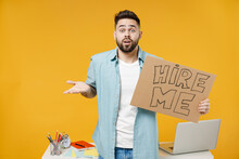 Young Confused Employee Business Man 20s Wearing Shirt Stand Work White Office Desk With Pc Laptop Hold Cardboard Sign Card Need Job, Hire Me Spread Hand Isolated On Yellow Background Studio Portrait.