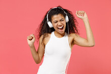 Young Smiling Happy Cheerful Satisfied Positive African American Woman 20s Wearing Basic Casual White Tank Shirt Headphones Listen To Music Dancing Isolated On Pink Color Background Studio Portrait