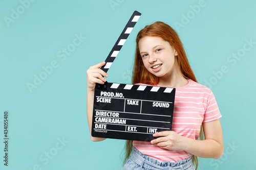 Foto Little cool redhead kid girl 12-13 years old wear pink striped t-shirt holding classic black film making clapperboard isolated on pastel blue background studio