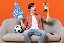 Young Amazed Man Football Fan In Shirt Support Team With Soccer Ball Sit Home Sofa Watch Tv Live Stream Hold Foam Glove Finger Champion Cup Isolated On Orange Background People Leisure Sport Concept