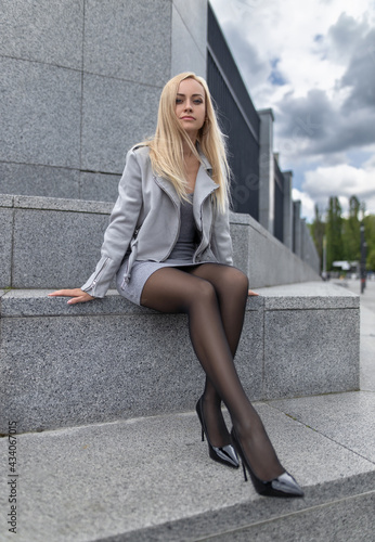 Fotografie, Obraz Blonde woman with perfect legs in pantyhose and shoes with high heels posing at the city square