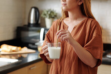 Young Woman Using Reusable Bamboo Straw When Drinking Cup Of Milk