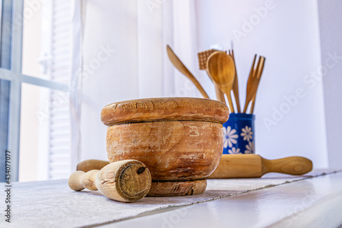 Photo Closeup of old wooden mortar with pestle inside on white table with grey tablecloth