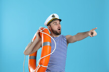 Surprised Sailor With Ring Buoy On Light Blue Background