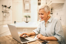 Portrait Of Focused Stylish Middle Aged Female Using Portable Computer For Distant Work Or Online Course, Learning New Marketing Skills, Making Notes In Copybook, Having Concentrated Facial Expression