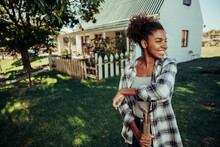 African American Female Standing In Farm Village Leaning On Pitch Fork Smiling In Luscious Green Land